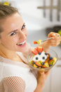 Smiling young housewife eating fresh fruit salad rear view in modern kitchen Stock Photos