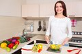 Smiling young housewife mixing fresh salad at kitchen Stock Photography