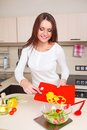 Smiling young housewife mixing fresh salad Royalty Free Stock Photo