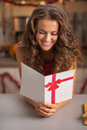 Smiling young housewife reading christmas postcard in kitchen red dress Royalty Free Stock Images