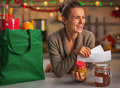 Smiling young housewife with receipts from christmas purchases in kitchen Royalty Free Stock Photos