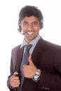 Smiling young indian call center executive operator man with headsets working Stock Photo