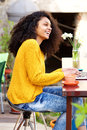 Smiling young lady at coffee shop with laptop Royalty Free Stock Photo