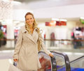 Smiling young lady with shopping bag near an escal Royalty Free Stock Image