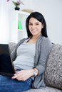 Smiling young lady sitting on sofa, using laptop Royalty Free Stock Photography