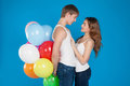 Smiling young love couple holding balloons studio over blue background Royalty Free Stock Photography