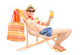 Smiling young male on a beach chair drinking cocktail isolated white background Royalty Free Stock Photo