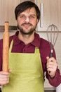 Smiling young man with apron holding a beater and a rolling pin in his kitchen Royalty Free Stock Images