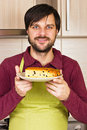 Smiling young man with apron holding a plate with homemade cake in his kitchen Stock Image
