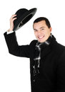 Smiling young man in black coat and scarf holding the hat isolat Stock Photos