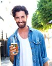 Smiling young man in blue shirt holding glass of beer portrait a Royalty Free Stock Image