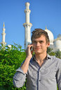 Smiling young man with a cell phone in front of mosque standing greens and white towers and domes Stock Image