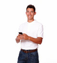 Smiling young man with a cellphone in t shirt is texting on his against white background Royalty Free Stock Image