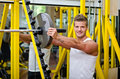 Smiling young man in gym putting weight disc on barbell handsome disck looking at camera Stock Images