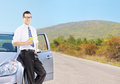 Smiling young man on his automobile relaxing and drinking coffee an open road shot with a tilt shift lens Royalty Free Stock Photos