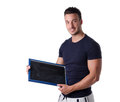 Smiling young man holding and showing blank blackboard empty looking in camera Royalty Free Stock Photos