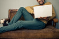 Smiling young man with laptop on old sofa is sitting an vintage and working his Royalty Free Stock Photos