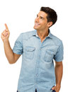 Smiling young man pointing upwards against white background vertical shot Stock Photo