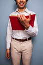Smiling young man reading a red book in shirt and tie is standing with Stock Photos