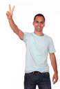 Smiling young man showing you victory sign portrait of a on white background Royalty Free Stock Photography