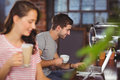 Smiling young man sitting at bar and using laptop men coffee shop Stock Photos