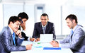 Smiling young man sitting at a business men meeting with colleagues Royalty Free Stock Photo