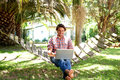 Smiling young man sitting in hammock with laptop Royalty Free Stock Photo