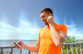 Smiling young man with smartphone and earphones Royalty Free Stock Photo