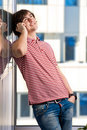 Smiling young man speaking on cellphone Royalty Free Stock Image