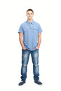 Smiling young man standing with hands in pockets full length portrait of isolated on white background Royalty Free Stock Photography