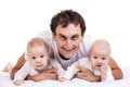 Smiling young man with two baby boys over white men background Royalty Free Stock Photography