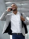 Smiling young man walking and talking on mobile phone Royalty Free Stock Photo