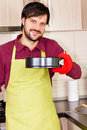 Smiling young man wearing cooking mitten and apron holding a bak baking tray at home Stock Photos