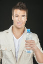 Smiling young man white shirt holding bottle water isolated black background Royalty Free Stock Photo