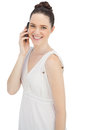Smiling young model in white dress having phone call on background Royalty Free Stock Photos