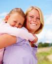 Smiling young mother carrying a girl on her back Stock Photos