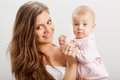 Smiling young mother  holding her baby girl Royalty Free Stock Image