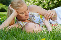 Smiling young mother reclines green grass next to her baby daughter Royalty Free Stock Images