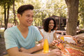 Smiling young multiethnic friends students outdoors drinking juice eating pizza. Royalty Free Stock Photo