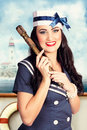 Smiling young pinup sailor girl american navy vintage picture of a in marine uniform holding nautical telescope on maritime ship Stock Photo