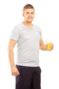 Smiling young sportsman posing with a glass of juice orange isolated against white background Royalty Free Stock Photos