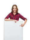Smiling young teenage girl with white blank board happiness advertising and people concept pointing finger to Stock Image