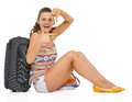 Smiling young tourist woman sitting near wheel bag framing hands Stock Image