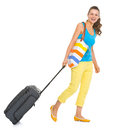 Smiling young tourist woman wheel bag going sideways Stock Images