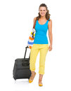 Smiling young tourist woman wheel bag going straight Stock Images