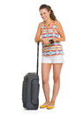 Smiling young tourist woman wheel bag listening music Stock Photos