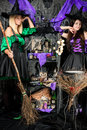Smiling young witches with broomsticks and potions Royalty Free Stock Photo