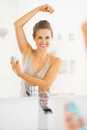 Smiling young woman applying deodorant on underarm in modern bathroom Stock Images