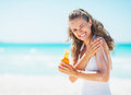 Smiling young woman applying sun block creme on beach sandy Stock Photos