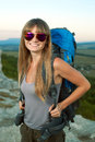 Smiling young woman with backpack in the mountains portrait of a sunset sky as background Stock Images